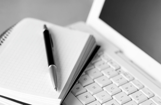 Ordinateur portable et cahier avec un stylo posé dessus