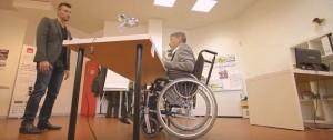 Personne valide debout et personne en fauteuil roulant assis de l'autre côté du bureau